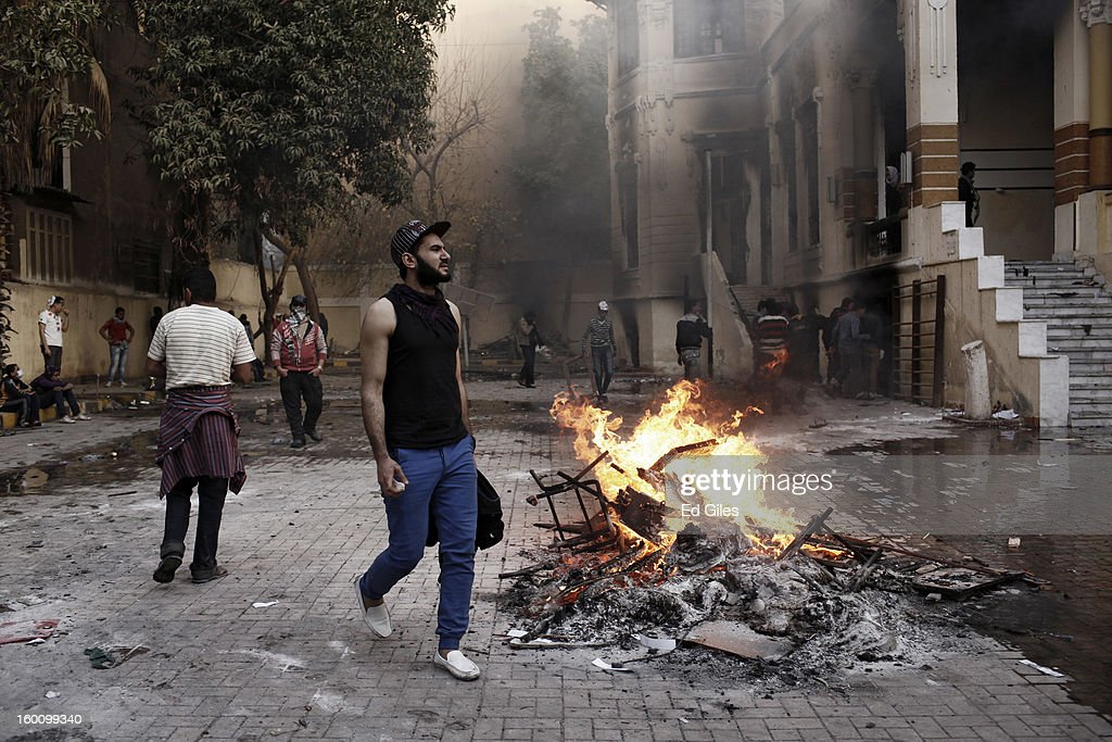 An Egyptian protester walks past a fire lit in the grounds of a school during a protest following the announcement of the death penalty for 21 suspects in connection with a football stadium massacre last year, on January 26, in Cairo, Egypt. Protests have continued across Egypt after a verdict was announced in a case over the deaths of more than seventy fans of Egypt's Al-Ahly football club in a stadium massacre on February 1, 2012, in the northern city of Port Said, during a brawl that began minutes after the final whistle of a match between Al-Ahly and opposing side, Al-Masry. 21 fans of the opposing side, Al-Masry, were given the death penalty in the court case, a verdict that must now be approved by Egypt's Grand Mufti. The verdict was handed down during a period of high tension across Egypt, one day after the second anniversary of the beginning of Egypt's 2011 revolution that overthrew former President, Hosni Mubarak.