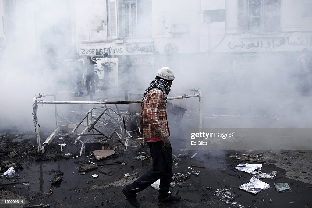 An Egyptian protester walks through a cloud of tear gas fired by Egyptian riot police during a protest following the announcement of the death penalty for 21 suspects in connection with a football stadium massacre last year, on January 26, in Cairo, Egypt. Protests have continued across Egypt after a verdict was announced in a case over the deaths of more than seventy fans of Egypt's Al-Ahly football club in a stadium massacre on February 1, 2012, in the northern city of Port Said, during a brawl that began minutes after the final whistle of a match between Al-Ahly and opposing side, Al-Masry. 21 fans of the opposing side, Al-Masry, were given the death penalty in the court case, a verdict that must now be approved by Egypt's Grand Mufti. The verdict was handed down during a period of high tension across Egypt, one day after the second anniversary of the beginning of Egypt's 2011 revolution that overthrew former President, Hosni Mubarak.