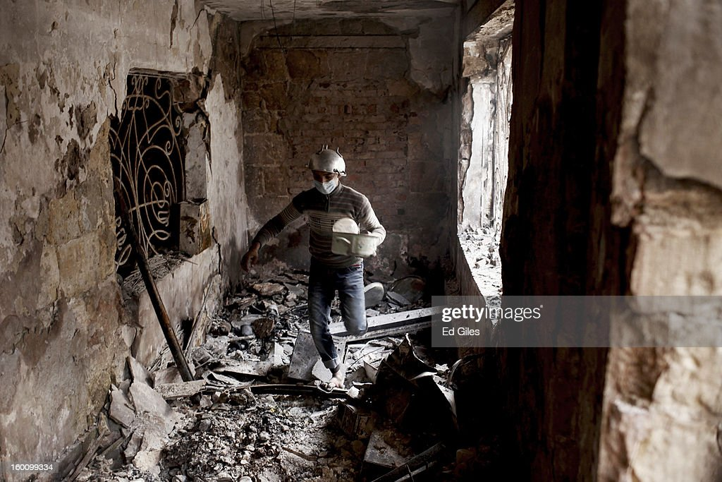 An Egyptian protester walks through a damaged school building during a demonstration following the announcement of the death penalty for 21 suspects in connection with a football stadium massacre last year, on January 26, in Cairo, Egypt. Protests have continued across Egypt after a verdict was announced in a case over the deaths of more than seventy fans of Egypt's Al-Ahly football club in a stadium massacre on February 1, 2012, in the northern city of Port Said, during a brawl that began minutes after the final whistle of a match between Al-Ahly and opposing side, Al-Masry. 21 fans of the opposing side, Al-Masry, were given the death penalty in the court case, a verdict that must now be approved by Egypt's Grand Mufti. The verdict was handed down during a period of high tension across Egypt, one day after the second anniversary of the beginning of Egypt's 2011 revolution that overthrew former President, Hosni Mubarak.