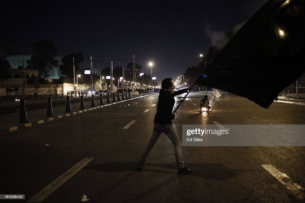 An Egyptian protester waves a large flag in the direction of nearby Egyptian riot police during violent protests at the Presidential Palace in Heliopolis on February 8, 2013, in Cairo, Egypt. Protests continued across Egypt against President Morsi and the Muslim Brotherhood two weeks after the second anniversary of the Egyptian Revolution that overthrew former President Hosni Mubarak on January 25, 2011.(Photo by Ed Giles/Getty Images).
