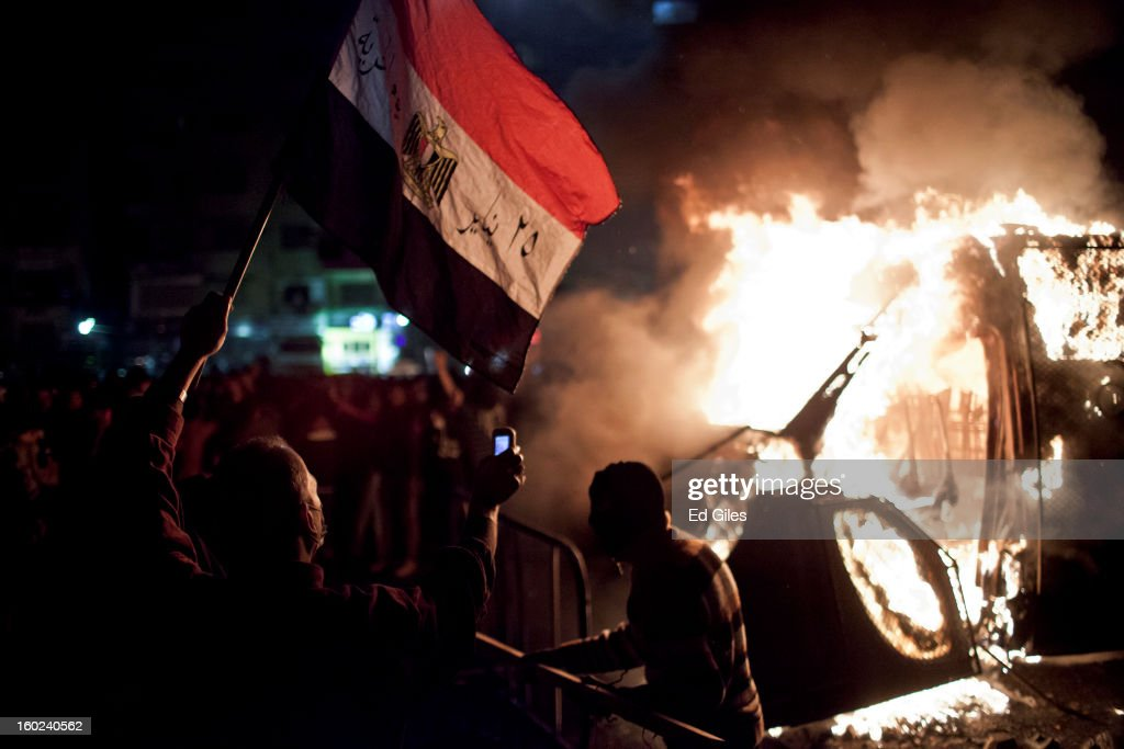 An Egyptian protester waves an Egyptian flag and films using a mobile phone as armoured Egyptian riot police vehicle of the, or Central Security Forces, that had been stolen then lit on fire during clashes nearby, in Tahrir Square on January 28, 2013 in Cairo, Egypt. Violent protests continued across Egypt three days after the second anniversary of the Egyptian Revolution that overthrew former President Hosni Mubarak and two days after 21 men sentenced to death in connection with the deaths of 74 football fans during riots at Port Said stadium one year ago.
