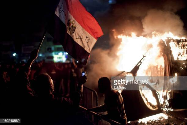 An Egyptian protester waves an Egyptian flag and films using a mobile phone as armoured Egyptian riot police vehicle of the or Central Security...