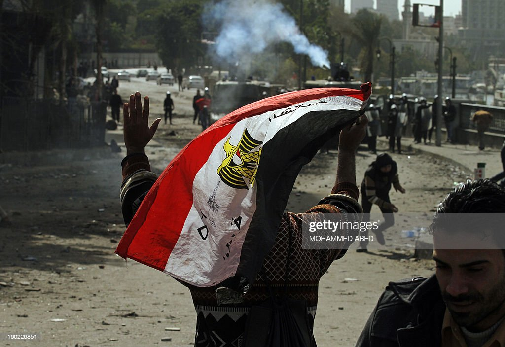 An Egyptian protester waves his national flag as he gestures towards riot police during clashes near Cairo's Tahrir Square on January 28, 2013. Egypt's cabinet approved a draft law that would allow President Mohamed Morsi to deploy the armed forces on the streets 'to participate with the police in preserving security and protecting vital establishments.'