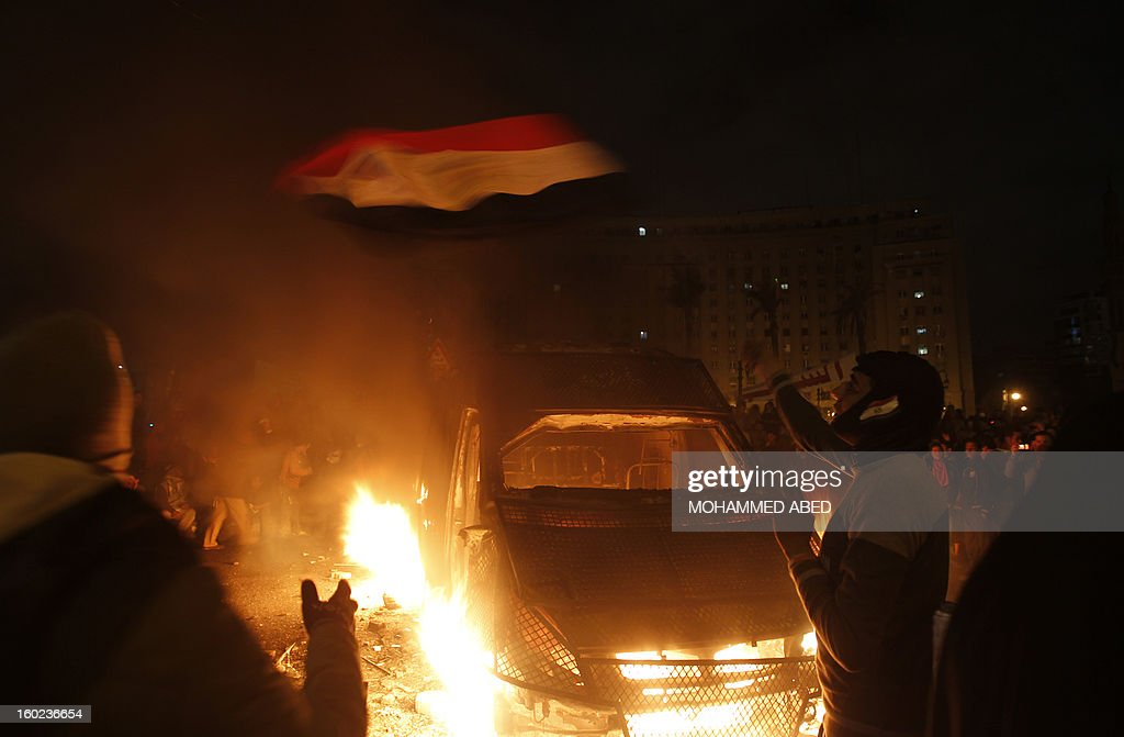 An Egyptian protester waves his national flag near a police vehicle on fire in Cairo's Tahrir Square on January 28, 2013. Egypt's main opposition bloc rejected an invitation by President Mohamed Morsi for talks on the violence and political turmoil sweeping the country and instead called for fresh mass demonstrations. AFP PHOTO/MOHAMMED ABED