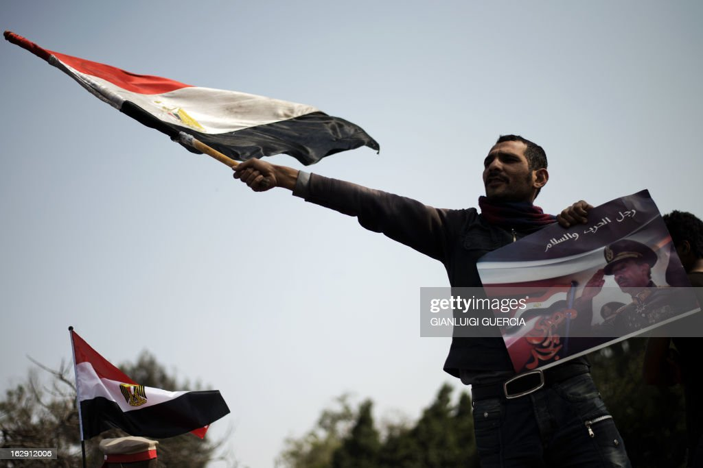 An Egyptian protester waves his national flag while holding a poster of slain former Egyptian president Anwar Sadat with a slogan reading in Arabic 'Man of war and peace' during a demonstration in support of the Egyptian army and against the Muslim Brotherhood in Cairo on March 1, 2013. On almost every Friday -- the first day of the Egyptian weekend -- opposition groups have called protests against President Mohamed Morsi and his powerful Muslim Brotherhood, which have regularly degenerated into violence. AFP PHOTO/GIANLUIGI GUERCIA