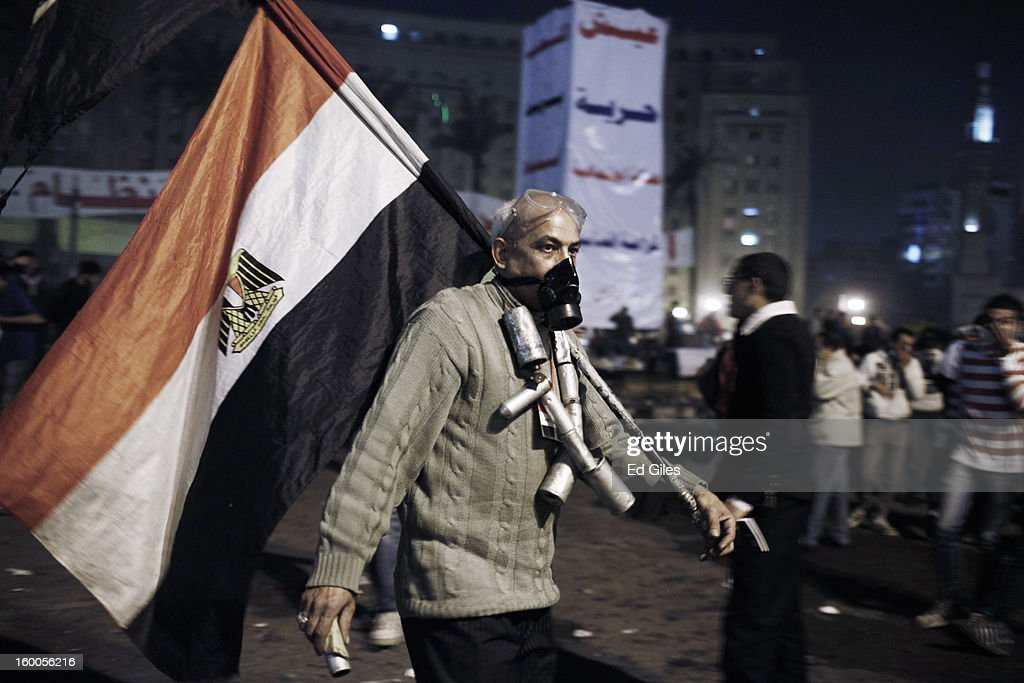 An Egyptian protester wearing empty tear gas canisters around his neck carries an Egyptian flag during a demonstration in Tahrir Square on January 25, in Cairo, Egypt. Thousands of protesters converged on the capital's iconic Tahrir Square on January 25, to mark the second anniversary of the overthrow of former President Hosni Mubarak's regime. (Photo by Ed Giles/Getty Images).