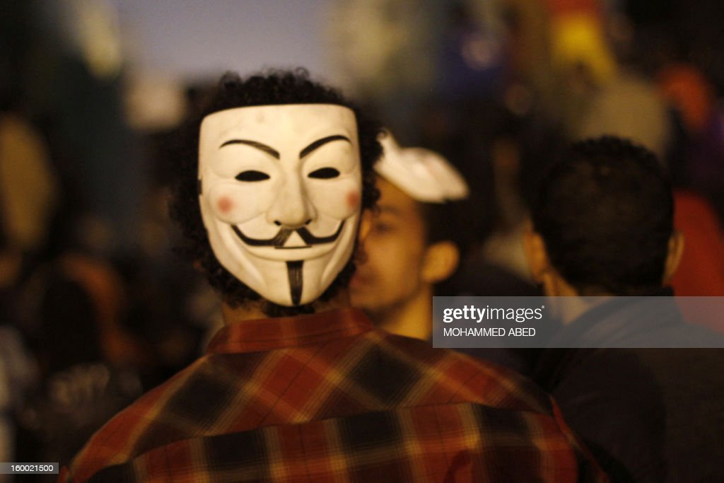 An Egyptian protester wears a mask of the anonymous movement during a protest in Tahrir Square to call for the fall of Islamist President on January 24, 2012 in Cairo. Police clashed with protesters in Cairo earlier, on the eve of the the second anniversary of the uprising that overthrew Hosni Mubarak, as they tried to dismantle a security barrier and called for the fall of President Mohamed Morsi. AFP PHOTO/MOHAMMED ABED