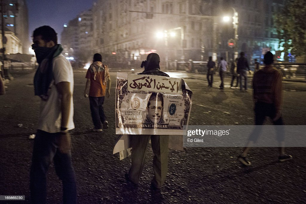 An Egyptian protester wears a poster showing the face of Egyptian President Mohamed Morsi on a United States one dollar bill during a demonstration against Morsi and the government of the Muslim Brotherhood by the Cairo High Court on April 6, 2013 in Cairo, Egypt. Hundreds of protesters gathered at multiple locations across Cairo and other cities in Egypt to mark the fifth anniversary of the April 6 movement, a major revolutionary group made up of youth and workers in Egypt.