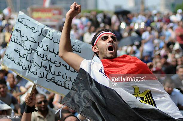 An Egyptian protester wrapped with his national flag shouts slogans in Cairo's Tahrir Square on September 30 2011 during a mass rally to reclaim the...
