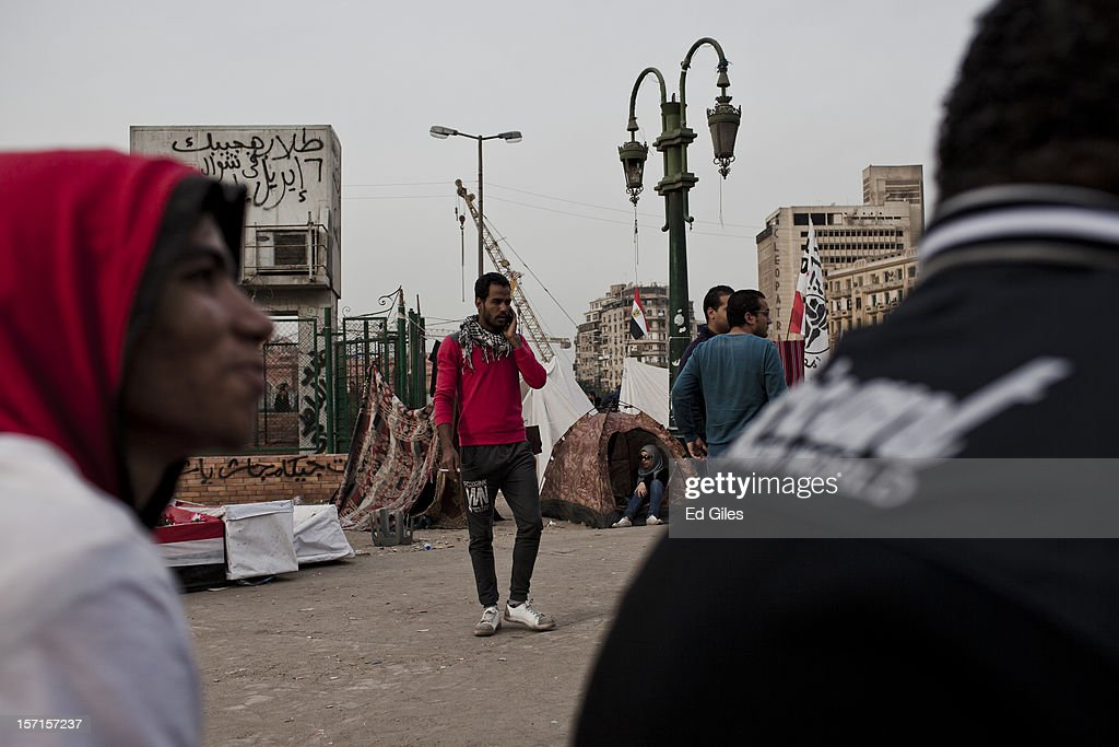 An Egyptian protesters speaks on a mobile phone near Tahrir Square on November 29, 2012, in Cairo, Egypt. Demonstrations continue in Cairo after more than a week of violent protests in response to Egyptian president Mohammed Morsi having awarded himself new constitutional powers, which many believe have been pushed through by the Muslim Brotherhood without inclusive consultation with other members of Egypt's cabinet and political leadership. (Photo by Ed Giles/Getty Images).