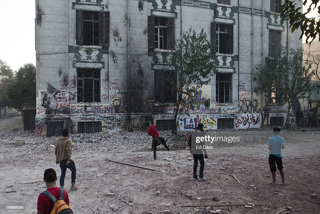 An Egyptian protesters throw rocks toward Egyptian riot police sheltering in a school building during violent protests near Tahrir Square, on November 23, 2012 in Cairo, Egypt. Thousands of Egyptian protesters gathered in central Cairo's Tahrir Square on Friday to protest against a new constitutional declaration issued yesterday by Egyptian president Mohammed Morsi, giving him sweeping powers, and extending the period of deadline for the drafting of Egypt's new constitution by two months. The seven-article declaration renders the president's decrees and laws immune from appeal or cancellation. It also protects both Egypt's Shura Council and Islamist-dominated Constituent Assembly from dissolution by the country's judicial authorities. The demonstration follows a week of violent protests in central Cairo, commemorating one year since a series of deadly protests named 'Mohammed Mahmoud', after the street they took place in, during November 2011.