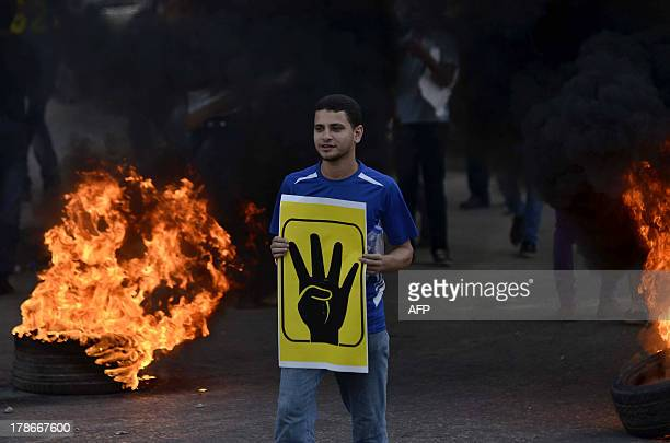 An Egyptian protestor hold a slogan symbolising the Rabaa alAdawyia mosque sit in during clashes between supporters of the Muslim Brotherhood and...