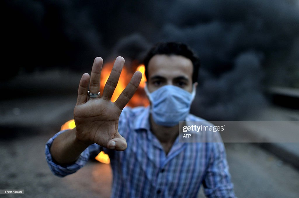 An Egyptian protestor shows his four fingers symbolising the Rabaa alAdawyia mosque sitin during clashes between supporters of the Muslim Brotherhood...