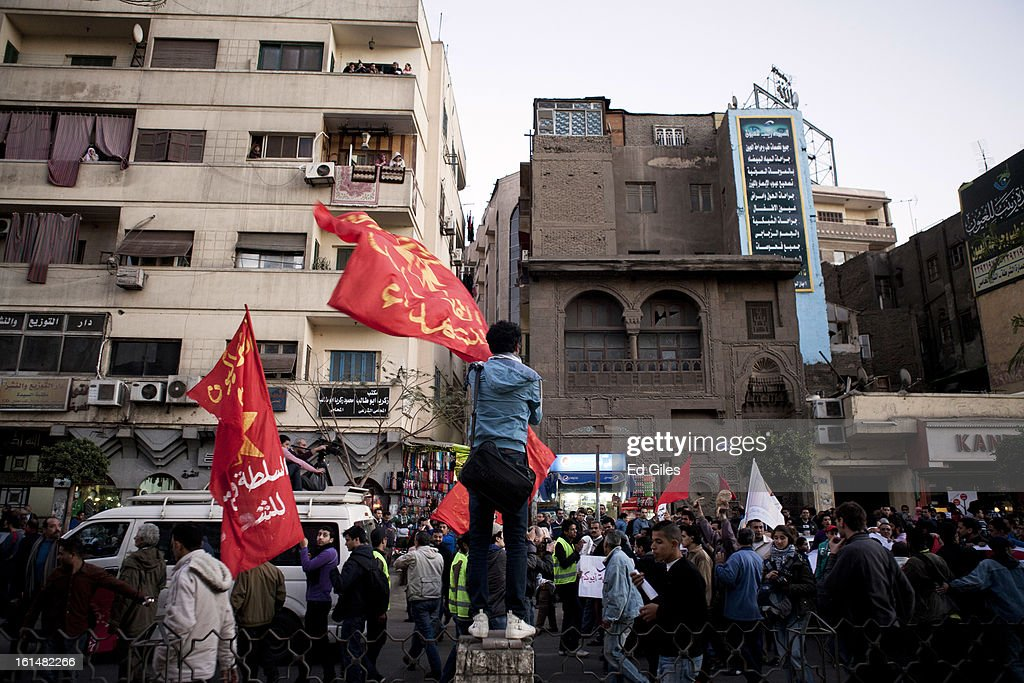 An Egyptian proteter waves a banner over the heads of other demonstrators during a protest march February 11, 2013 in Cairo, Egypt. Protests continued across Egypt against President Morsi and the Muslim Brotherhood on the 2nd anniversary of former President Hosni Mubarak stepping down, and over two weeks after the second anniversary of the Egyptian Revolution beginning on January 25, 2011. (Photo by Ed Giles/Getty Images).
