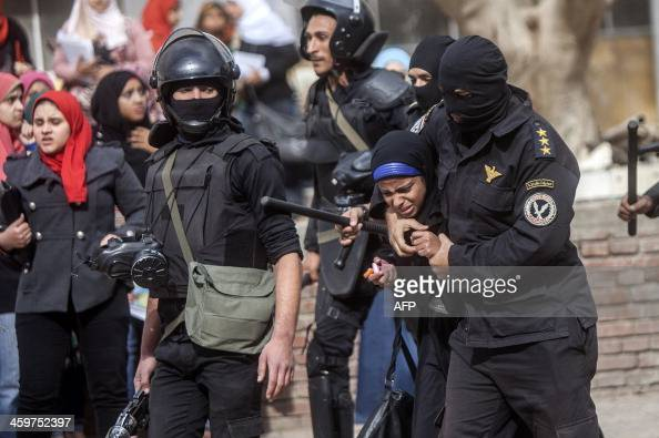 An Egyptian riot policeman detains a female student of alAzhar University during a protest by students who support the Muslim Brotherhood inside...
