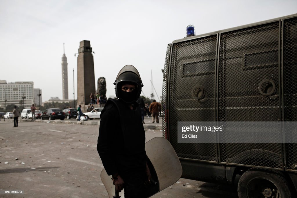 An Egyptian riot policeman stands by an armoured vehicle during a demonstration in Tahrir Square on January 27, 2013 in Cairo, Egypt. Violent protests continued across Egypt two days after the second anniversary of the Egyptian Revolution that overthrew former President Hosni Mubarak on January 25, and one day after the announcement of the death penalty for 21 suspects in connection with a football stadium massacre one year before. The verdict was announced in a case over the deaths of more than seventy fans of Egypt's Al-Ahly football club in a stadium massacre on February 1, 2012, in the northern city of Port Said, during a brawl that began minutes after the final whistle of a match between Al-Ahly and opposing side, Al-Masry. 21 fans of the opposing side, Al-Masry, were given the death penalty, a verdict that must now be approved by Egypt's Grand Mufti. (Photo by Ed Giles/Getty Images).