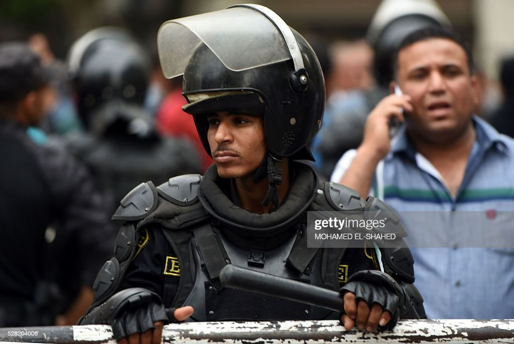 An Egyptian riot policeman stands guard during a protest of journalists demanding the sacking of the interior minister on May 4, 2016 outside the Journalists' Syndicate headquarters in Cairo, after an unprecedented police raid to arrest two reporters. Egyptian police stormed the headquarters of the journalists' association in central Cairo on May 1, 2016 and arrested two journalists, Amr Badr and Mahmud el-Sakka, for incitement to protest. / AFP / MOHAMED