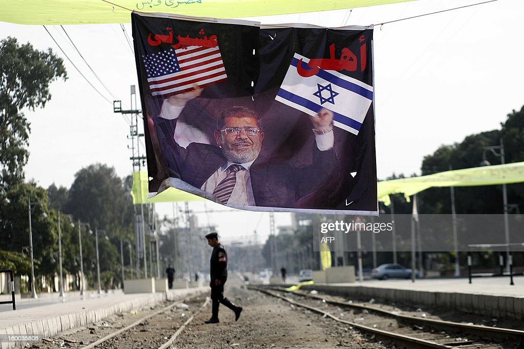 An Egyptian riot policeman walks past a giant poster of President Mohamed Morsi during a protest to demand change, two years after the uprising that ousted Hosni Mubarak and ushered in an Islamist government on January 25, 2013 in Cairo. Marches from several parts of the capital headed for Tahrir Square, with protesters carrying huge Egyptian flags in scenes reminiscent of the 2011 protests.