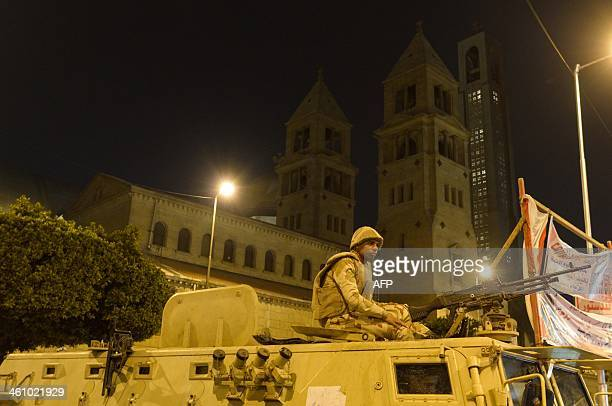 An Egyptian solder sets atop an armored vehicle guarding the alAbasseya Cathedral in Cairo late on January 6 2014 as Egypts Coptic Christians attend...