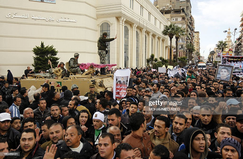 An Egyptian soldier standing on a armoured personel carrier (APC) gestures towards Egyptian protesters shouting slogans against Egypt's President Mohamed Morsi during a demonstration after Friday prayers in Port Said on February 1, 2013. Thousands of Egyptians flooded the streets in a show of opposition to the Islamist President and his Muslim Brotherhood after a week of a wave of deadly unrest swept the country.