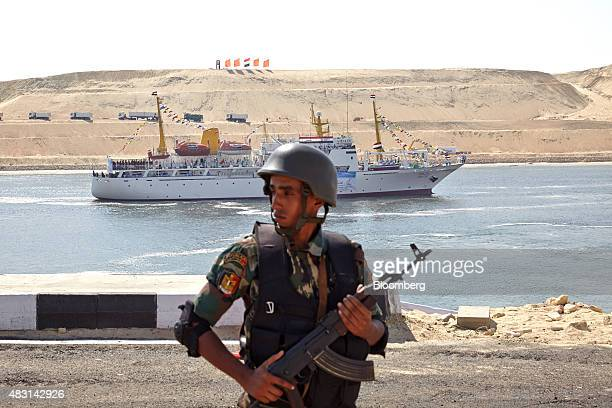 An Egyptian soldier stands guard as a ship goes through a section of the New Suez Canal operated by the Suez Canal Authority in Ismailia Egypt on...