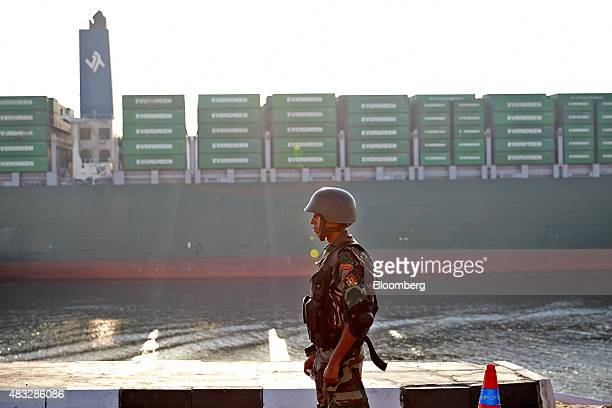 An Egyptian soldier stands guard as the Thalassa Avra container ship passes through the New Suez Canal operated by the Suez Canal Authority during...
