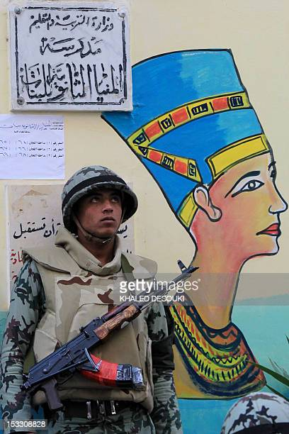 An Egyptian soldier stands guard in front of a mural of Queen Nefertiti as he secures the entrance to a polling station in Minya some 350 kms south...
