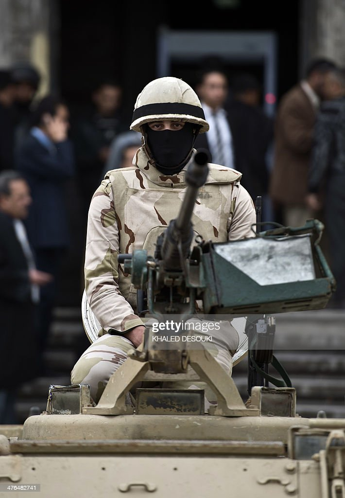 An Egyptian soldier stands guard on an armoured personnel carrier (APC) outside the criminal court in Egypt's Mediterranean city of Alexandria on March 3, 2014, during the retrial of the two policemen Awad Ismail Suleiman and Mahmoud Salah Mahoud, who are accused of using excessive force and killing 28-year-old blogger Khaled Said. The two policemen were sentenced to ten years in jail for the killing of the blogger whose death rallied protesters in the 2011 revolt that toppled Hosni Mubarak.