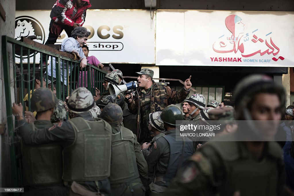An Egyptian soldier tries to calm down anti President Mohamed Morsi protesters as they try to bring down a barricade erected by the Egyptian army to protect the Presidential Palace in Cairo on December 11, 2012. Protesters gathered in Cairo for rival rallies over a deeply disputed constitutional referendum proposed by Egypt's Islamist president, Mohamed Morsi, raising fears of street clashes .
