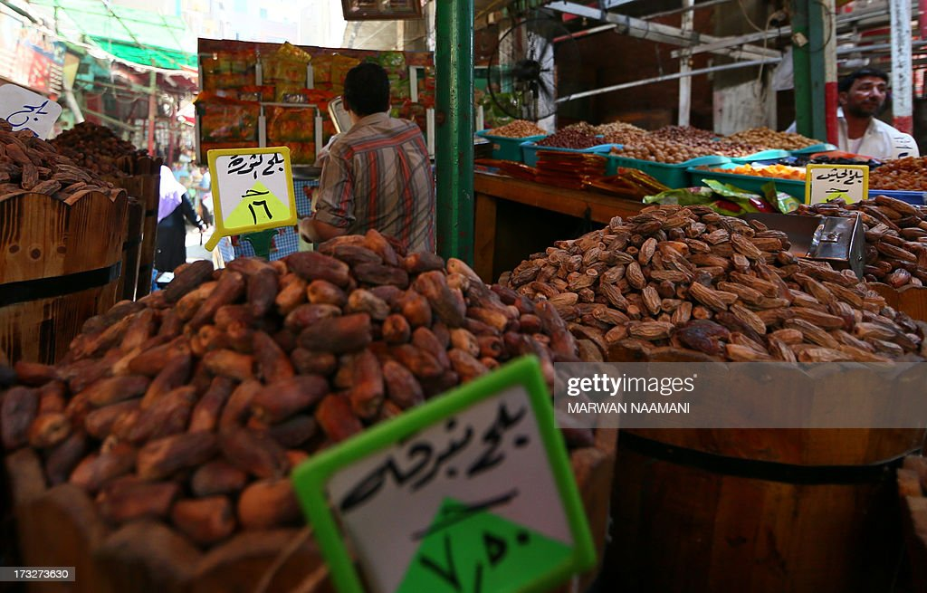 An Egyptian stands behind dates named 'al-Thawra' (back-L), which means 'revolution' in Arabic, and 'Jeish' (Back-R), which means 'army' in Arabic, at a shop in the working-class Saida Zeinab district in Cairo on the second day of the holy month of Ramadan July 11, 2013. During the Muslim fasting month of Ramadan Egyptians name the best and worst quality dates after personalities to lure customers. AFP PHOTO/MARWAN NAAMANI
