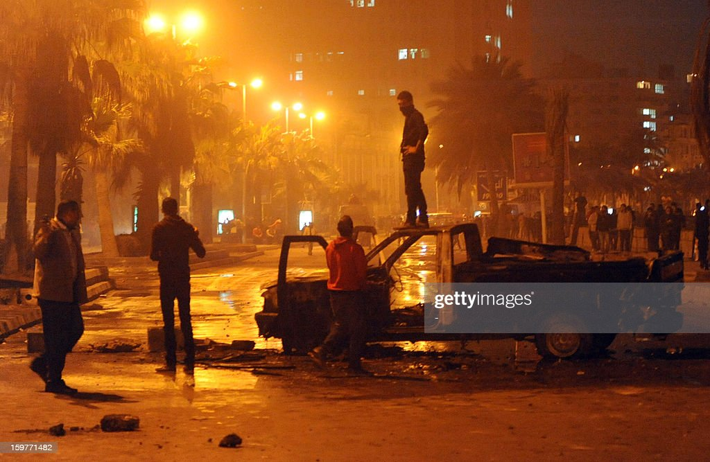 An Egyptian stands on a burnt out vehicle during clashes with the police in the coastal city of Alexandria on January 20, 2013. Clashes broke out for the second day at a court in Egypt's second city between protesters and security forces, as protesters demanded worthy verdicts for security officials on trial in the northern city for a deadly crackdown during the Arab Spring uprising two years ago.
