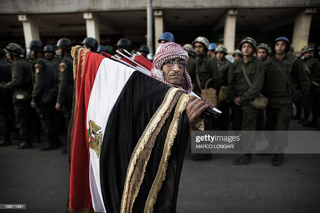 An Egyptian street vendor holding national flags walks past Egyptian soldiers in front of the Presidential Palace in Cairo on December 11, 2012. Protesters gathered in Cairo for rival rallies over a deeply disputed constitutional referendum proposed by Egypt's Islamist president, Mohamed Morsi, raising fears of street clashes . AFP PHOTO/MARCO LONGARI