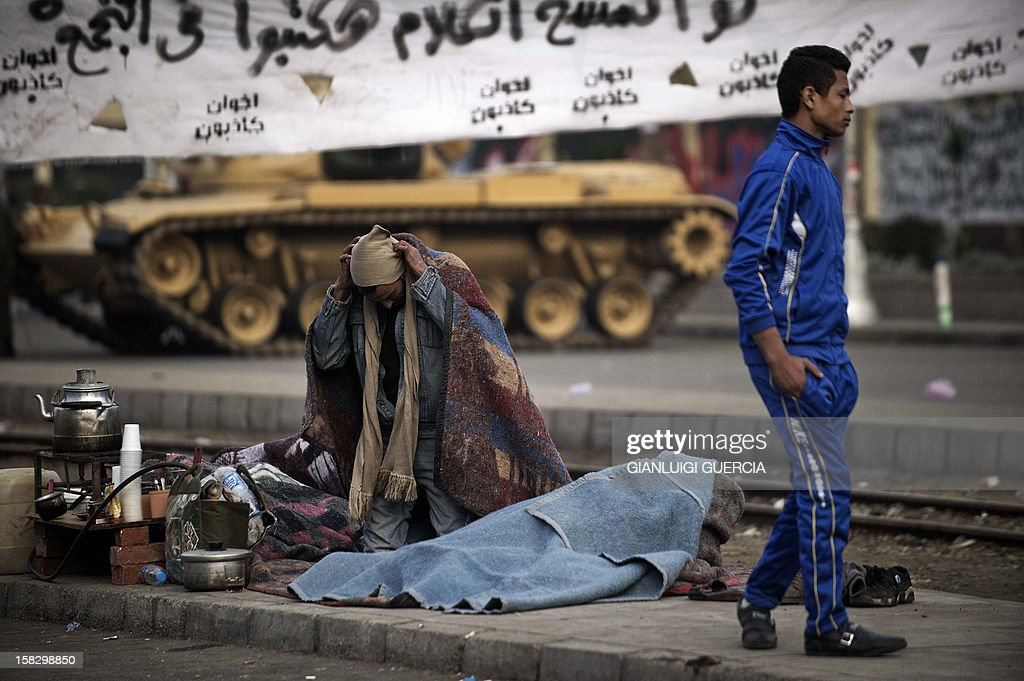 An Egyptian street vendor wakes up after spending the night outside near the presidential palace in Cairo on December 13, 2012. Egypt's crisis showed no sign of easing as the army delayed unity talks meant to ease political divisions and the opposition set near-impossible demands for taking part in a looming constitutional referendum. AFP PHOTO/GIANLUIGI GUERCIA
