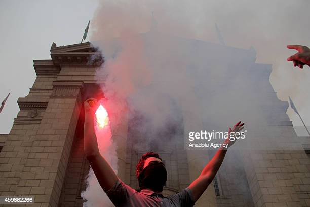 An Egyptian student holds up a flare during a protest against court verdict acquitting former president Hosni Mubarak at the Cairo University campus...