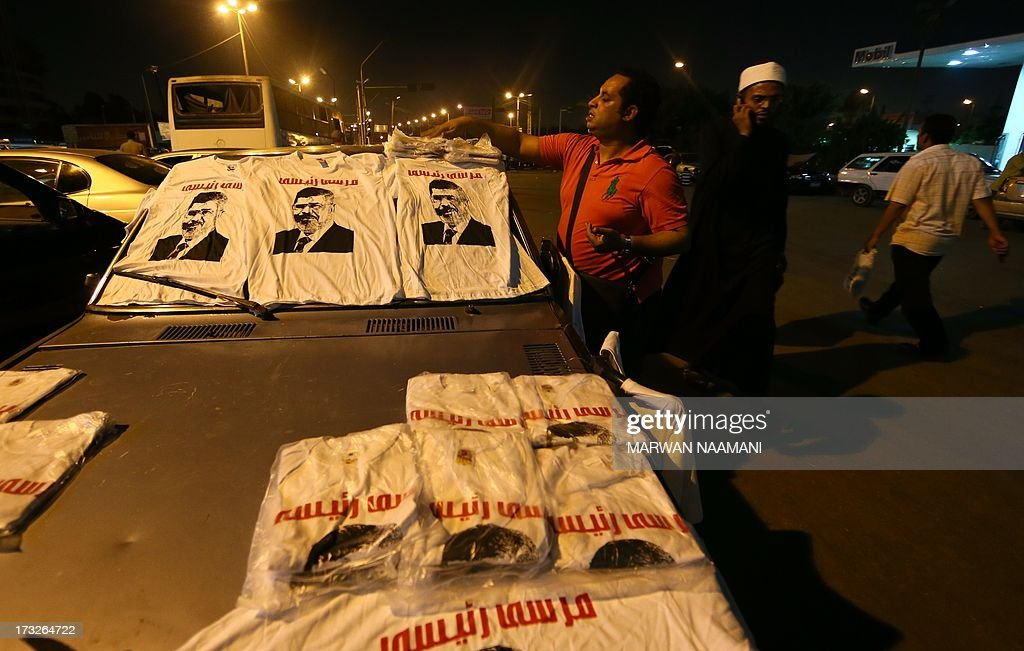 An Egyptian supporter of deposed president Mohamed Morsi diplays T-shirts with his portrait on a car during a rallye outside Cairo's Rabaa al-Adawiya mosque late June 10, 2013. Egypt's Prime Minister said on July 11 that he does not rule out posts for the Muslim Brotherhood in his cabinet if candidates are qualified, even as police cracked down on Morsi's Islamist group.