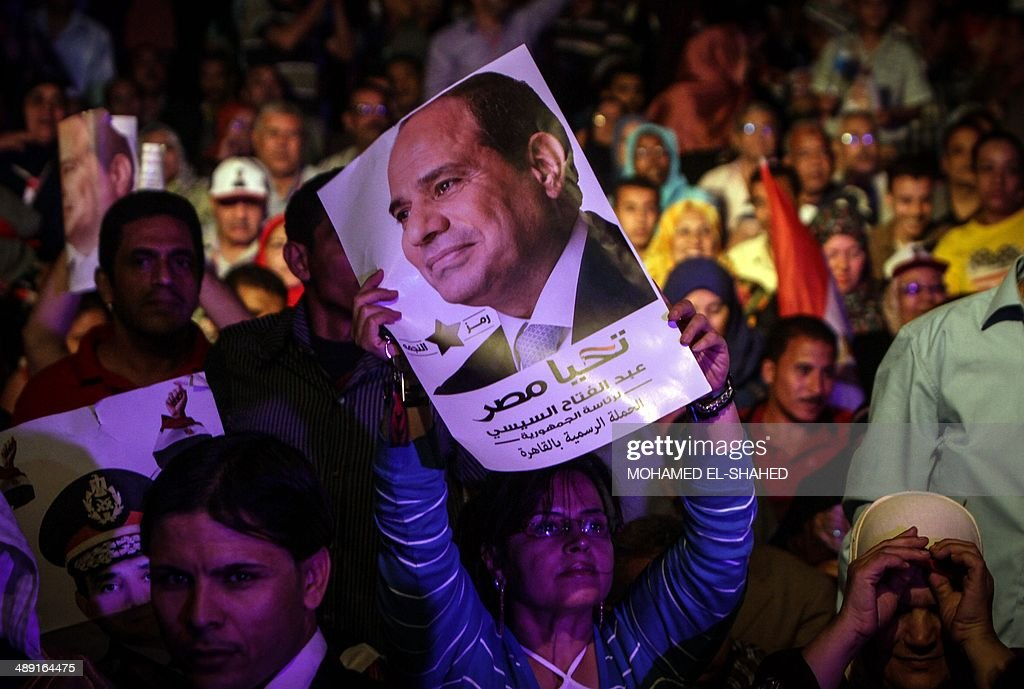 An Egyptian supporter of Egypt's former army chief Abdel Fattah al-Sisi holds his portrait during a gathering in the capital Cairo on May 10, 2014. The retired field marshal, who toppled elected Islamist president Mohamed Morsi in July, is expected to sweep the May 26-27 election.