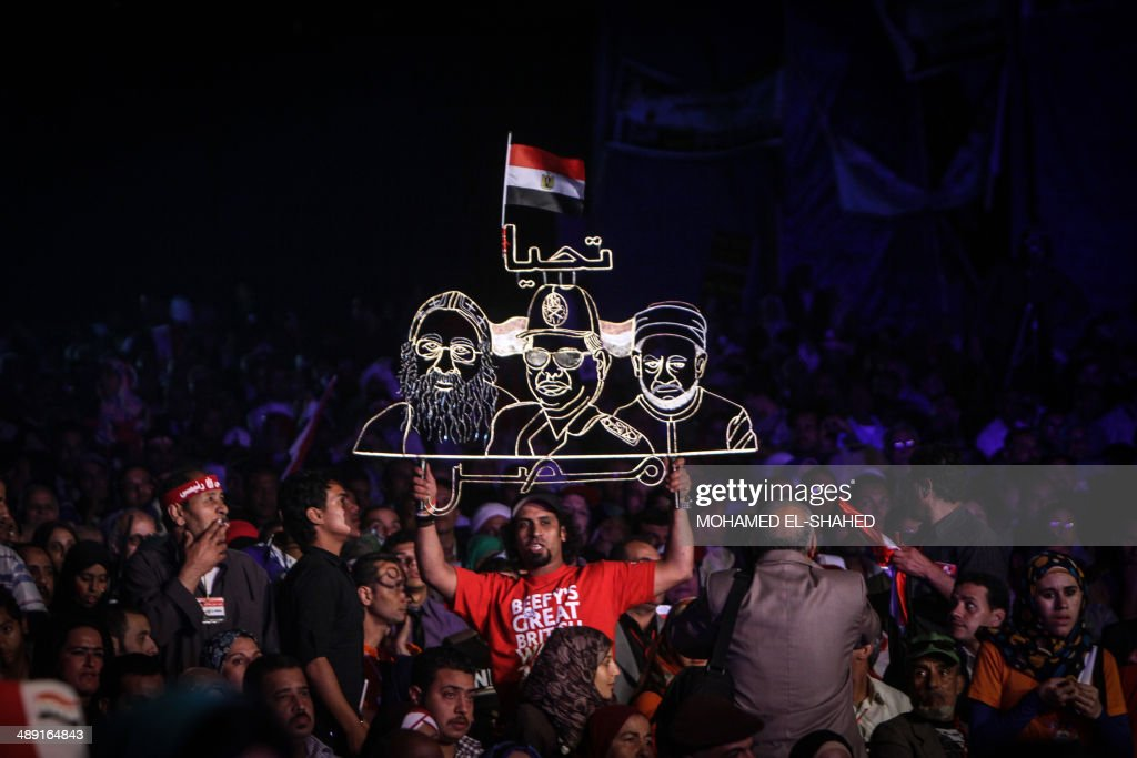 An Egyptian supporter of Egypt's former army chief Abdel Fattah al-Sisi holds a neon sign portraying him (C) along with Pope Tawadros II (L), leader of Egypt's Coptic Church, and Grand Imam of al-Azhar Shiekh Ahmed el-Tayeb (R) during a gathering in the capital Cairo on May 10, 2014. The retired field marshal, who toppled elected Islamist president Mohamed Morsi in July, is expected to sweep the May 26-27 election.