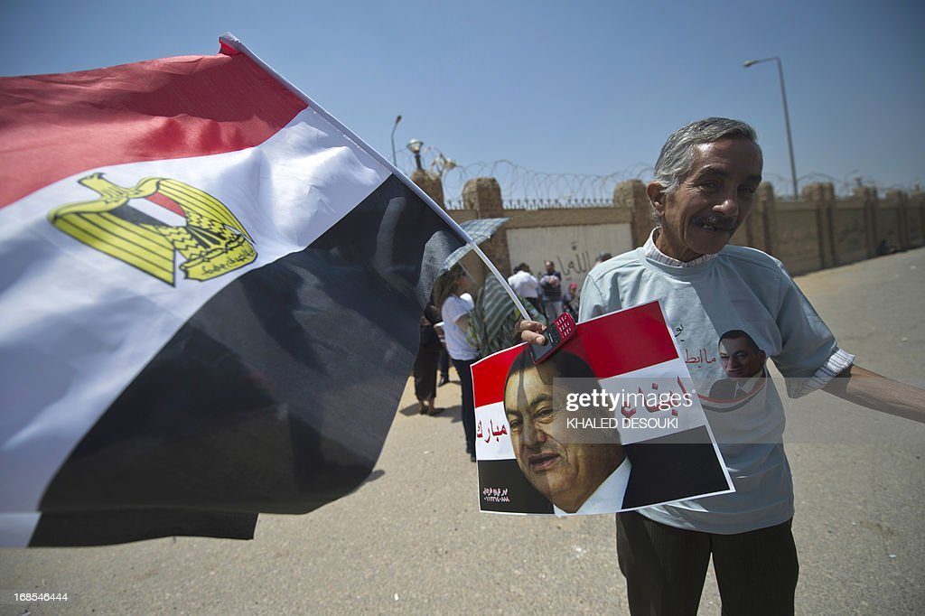 An Egyptian supporter of former Egyptian president Hosni Mubarak, holds a portrait of him and a national flag outside the Egyptian police academy in Cairo, where Mubarak's trial is taking place on May 11, 2013. Mubarak appeared in court to face a new trial for complicity in the murder of hundreds protesters during the 2011 uprising.