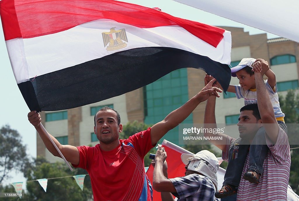 An Egyptian supporter of the Muslim Brotherhood and deposed president Mohamed Morsi waves a national flag during a rally outside Cairo's Rabaa al-Adawiya mosque on July 12, 2013, following Friday noon prayer. Activists for and against ousted Morsi have called rival rallies for the first Friday of Ramadan, as tensions soar over the army's overthrow of the Islamist leader.