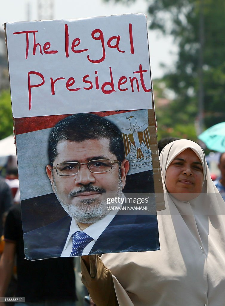 An Egyptian supporter of the Muslim Brotherhood and deposed president Mohamed Morsi shows his portrait on which is written 'The legal president' during a rally outside Cairo's Rabaa al-Adawiya mosque on July 12, 2013, following Friday noon prayer. Activists for and against ousted Morsi have called rival rallies for the first Friday of Ramadan, as tensions soar over the army's overthrow of the Islamist leader.