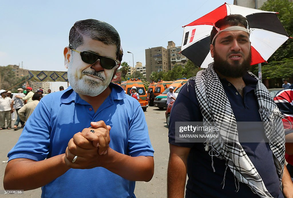 An Egyptian supporter of the Muslim Brotherhood and deposed president Mohamed Morsi sporting a cartoon mask of the toppled leader, guards with his colleague during a rally outside Cairo's Rabaa al-Adawiya mosque on July 12, 2013, following Friday noon prayer. Activists for and against ousted Morsi have called rival rallies for the first Friday of Ramadan, as tensions soar over the army's overthrow of the Islamist leader.