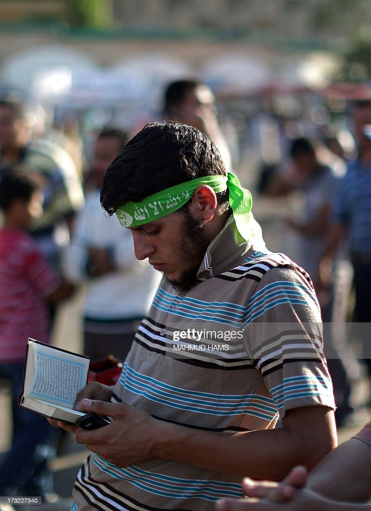 An Egyptian supporter of the Muslim Brotherhood reads the Koran, Islam's holy book, outside Cairo's Rabaa al-Adawiya mosque on July 10, 2013 before breaking the fast on the first day of Islam's holy month of Ramadan. Tens of millions across the Muslim world fast from dawn to dusk and strive to be more pious and charitable during the month, which ends with the eid holiday.
