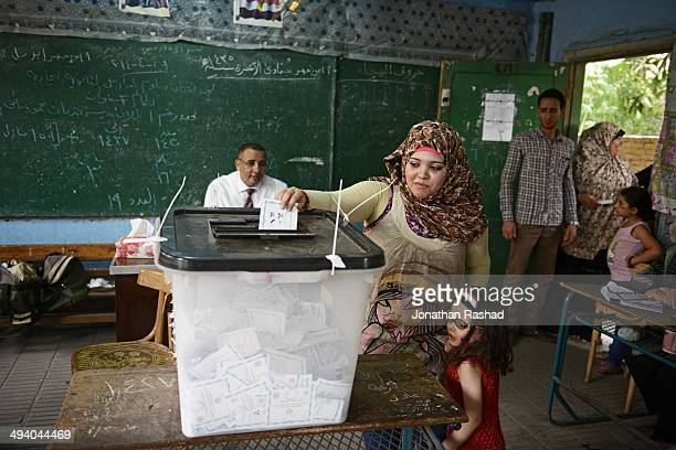 An Egyptian voter places her vote in the ballot box at a polling station in the Cairo suburb of Rod ElFarag on May 27 2014 in Cairo Egypt Egypt will...