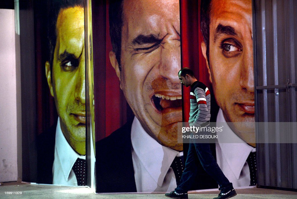An Egyptian walks past posters of Egyptian satirist Bassem Youssef outside a theatre in Cairo on January 22, 2013. The Cairo cafe is packed with patrons in stitches as television host Bassem Youssef fires his caustic criticism at President Mohamed Morsi, but post-revolution media freedoms have proved no laughing matter for some. Youssef, a heart surgeon turned comedian who enjoys a massive following, has now joined the ranks of several colleagues in the media who face charges of insulting the president.