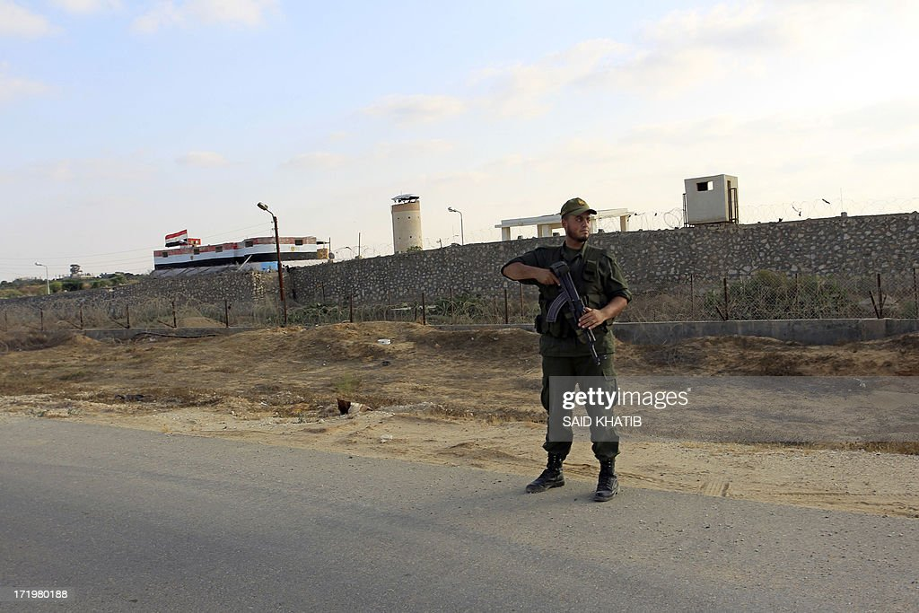 An Egyptian watch tower is seen in the background as Palestinian Hamas security forces patrol the Rafah area in the Gaza Strip on the border with Egypt on June 30, 2013. Hamas security forces boosted its security presence along the border between the Gaza Strip and Egypt as Egypt prepares for massive demonstrations organized by opponents of President Mohamed Morsi, demanding his 'departure' on the first anniversary of the coming to power. AFP PHOTO / SAID KHATIB.