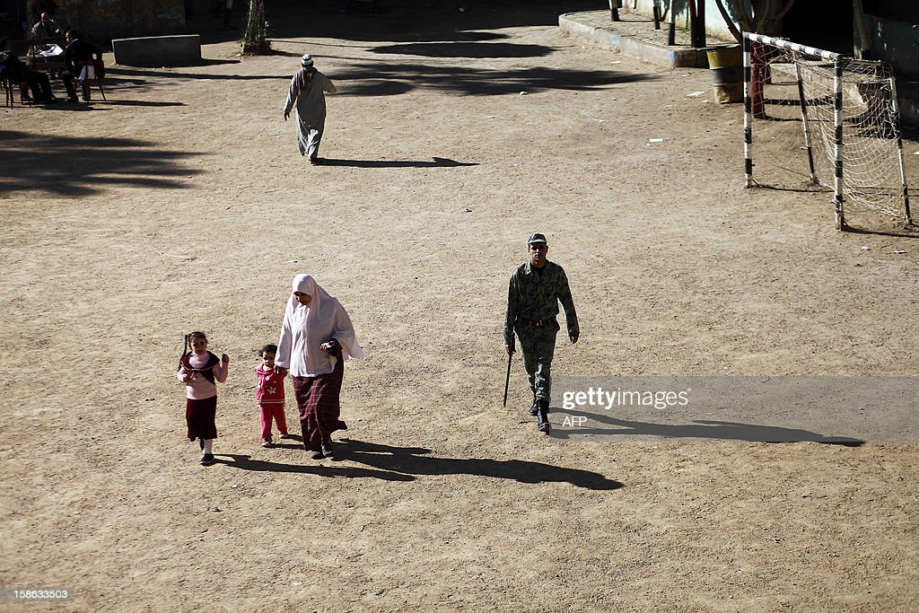 An Egyptian woman and her children walk past a soldier as they arrive at a polling station during the second round of a referendum on a new draft constitution in Beni Sueif, south of Cairo, on December 22, 2012. Egyptians are voting in the final round of a referendum on a new constitution championed by President Mohamed Morsi and his Islamist allies against fierce protests from the secular-leaning opposition. AFP PHOTO/MAHMUD KHALED