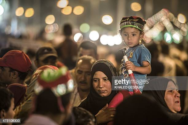 An Egyptian woman carries a girl on her shoulders outside Cairo's Sayeda Zainab mosque during the celebrations of the birthday of Prophet Mohamed's...