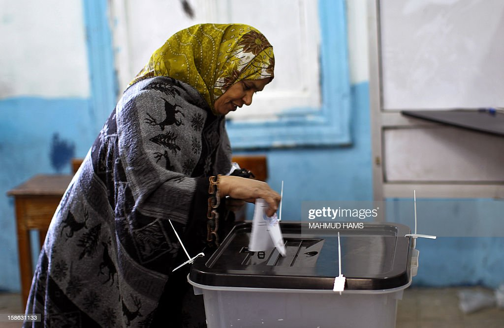 An Egyptian woman casts her ballot at a polling station during the second round of a referendum on a new draft constitution in Giza, south of Cairo, on December 22, 2012. Egyptians are voting in the final round of a referendum on a new constitution championed by President Mohamed Morsi and his Islamist allies against fierce protests from the secular-leaning opposition.