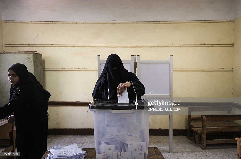 An Egyptian woman casts her ballot during a referendum on a new constitution at a polling station in President Mohamed Morsi's hometown Adwa in the Nile Delta on December 15, 2012. Egypt's opposition cried fraud in the first round of a divisive referendum on a new constitution, accusing Morsi's Muslim Brotherhood of rigging votes to adopt the Islamist-backed text. AFP PHOTO/GIANLUIGI GUERCIA