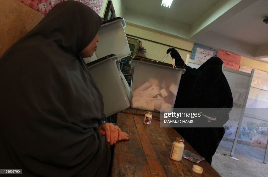 An Egyptian woman casts her ballot during the second round of a referendum on a new draft constitution in Giza, south of Cairo, on December 22, 2012. Egyptians are voting in the final round of a referendum on a new constitution championed by President Mohamed Morsi and his Islamist allies against fierce protests from the secular-leaning opposition. AFP PHOTO/MAHMUD HAMS